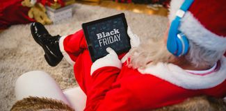 Composite image of black friday text with christmas icons on blackboard. Black Friday text with Christmas icons on blackboard against santa claus using digital Royalty Free Stock Photos