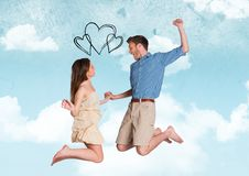 Composite image of black hearts and couple jumping with hearts against sky Royalty Free Stock Images