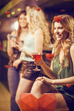 Composite image of blond woman drinking cocktail Royalty Free Stock Photos
