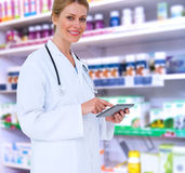 Composite image of blonde doctor using tablet pc. Blonde doctor using tablet pc against close up of shelves of drugs Stock Image