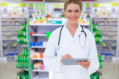 Composite image of blonde doctor using tablet pc. Blonde doctor using tablet pc against close up of shelves of drugs Stock Photos