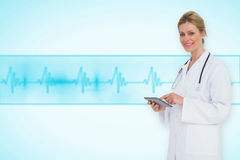 Composite image of blonde doctor using tablet pc Stock Photo