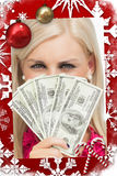 Composite image of blonde hiding her face with dollars banknotes Royalty Free Stock Photo