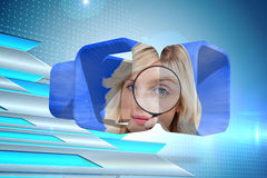 Composite image of blonde holding magnifying glass on abstract screen Stock Photography