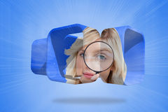 Composite image of blonde holding magnifying glass on abstract screen Stock Image