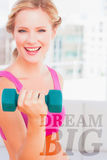 A Composite image of blonde lifting dumbbells and smiling at camera Stock Image