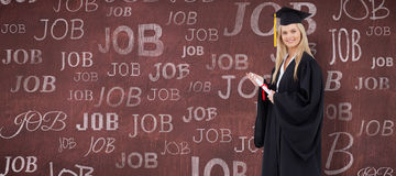 Composite image of blonde student in graduate robe holding a diploma Stock Photo
