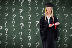 Composite image of blonde student in graduate robe holding her diploma Stock Photos