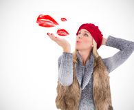 Composite image of blonde in winter clothes blowing kiss Stock Photography