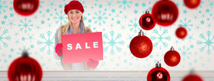 Composite image of blonde in winter clothes holding sale sign. Blonde in winter clothes holding sale sign against painted blue wooden planks Royalty Free Stock Photos