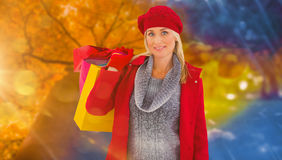 Composite image of blonde in winter clothes holding shopping bags Royalty Free Stock Image
