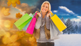 Composite image of blonde in winter clothes holding shopping bags Royalty Free Stock Photo
