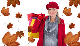 Composite image of blonde in winter clothes holding shopping bags Royalty Free Stock Photography