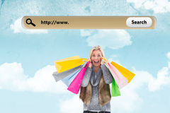 Composite image of blonde in winter clothes holding shopping bags Royalty Free Stock Images