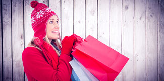 Composite image of blonde in winter clothes holding shopping bags. Blonde in winter clothes holding shopping bags against wooden planks Royalty Free Stock Image