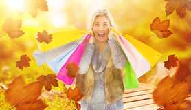 Composite image of blonde in winter clothes holding shopping bags Stock Photos