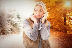 Composite image of blonde in winter clothes smiling Royalty Free Stock Photos