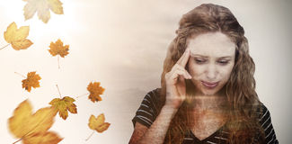 Composite image of blonde woman having headache. Blonde woman having headache against autumn leaves pattern Stock Images