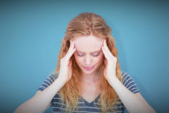 Composite image of a blonde woman having headache. A blonde woman having headache against blue background royalty free stock image