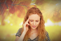 Composite image of blonde woman having headache. Blonde woman having headache against golden leaves Stock Photo