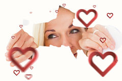 Composite image of blonde woman looking through torn paper. Blonde woman looking through torn paper against hearts stock photography