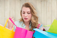Composite image of blonde woman opening gift bag and looking on it Stock Photo