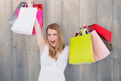 Composite image of blonde woman raising shopping bags Stock Images