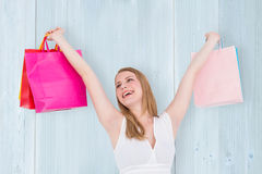 Composite image of blonde woman raising shopping bags Royalty Free Stock Photo