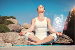 Composite image of blonde woman sitting in lotus pose on beach on mat Stock Photos