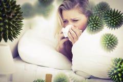 Composite image of blonde woman sneezing. Blonde woman sneezing against virus royalty free stock images