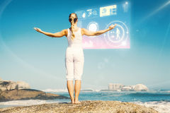Composite image of blonde woman standing on beach on rock with arms out Royalty Free Stock Image