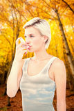 Composite image of blonde woman taking her inhaler Royalty Free Stock Images