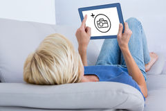 Composite image of blonde woman using her tablet on the couch. Blonde woman using her tablet on the couch against photography apps Royalty Free Stock Photo
