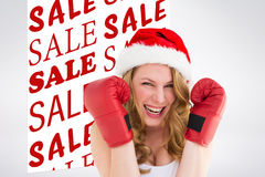 Composite image of blonde woman wearing boxing gloves smiling at camera Stock Images