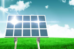 Composite image of blue solar panel. Blue solar panel against blue sky over green field Royalty Free Stock Photography