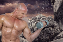 Composite image of bodybuilder concentrating while lifting dumbbells Stock Images