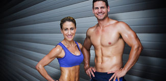 Composite image of bodybuilding couple. Bodybuilding couple against grey shutters Royalty Free Stock Images