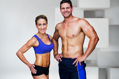 Composite image of bodybuilding couple. Bodybuilding couple against white tile design Stock Images