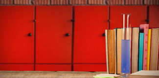 Composite image of books arranged on wooden table. Books arranged on wooden table against close-up of orange lockers royalty free stock images