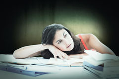 Composite image of bored female student doing her homework. Bored female student doing her homework against dark background Royalty Free Stock Photography