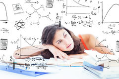 Composite image of bored female student doing her homework. Bored female student doing her homework against math and science doodles Stock Image