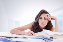 Composite image of bored student doing her homework. Bored student doing her homework against bright white hall with columns Royalty Free Stock Images