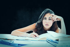 Composite image of bored student doing her homework. Bored student doing her homework against dark background Stock Images
