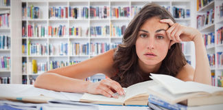 Composite image of bored student doing her homework. Bored student doing her homework against teacher reading books to her students Stock Photography