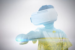 Composite image of boy clenching fist while using virtual reality glasses Stock Photography