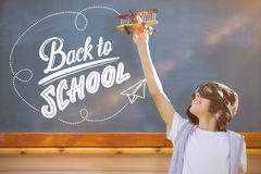 Composite image of boy playing with a toy aeroplane. Boy playing with a toy aeroplane against blackboard royalty free stock images
