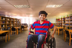Composite image of boy sitting in wheelchair in school corridor. Boy sitting in wheelchair in school corridor against view of library Stock Photo