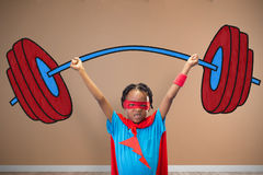 Composite image of boy in superhero disguise standing with hands raised Royalty Free Stock Photo