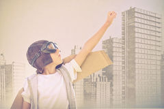 Composite image of boy wearing flying goggles with hand raised Stock Photos