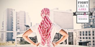 Composite image of breast cancer awareness message. Breast cancer awareness message against confident woman standing in city for breast cancer awareness stock photos